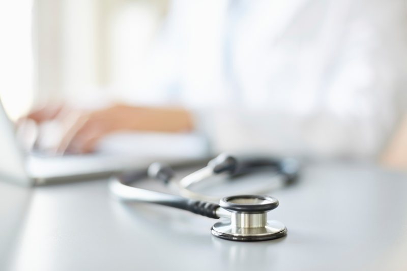 Close-up of stethoscope on desk with doctor using laptop in background. The female doctor is sitting at desk in hospital. The focus is on stethoscope in foreground.
